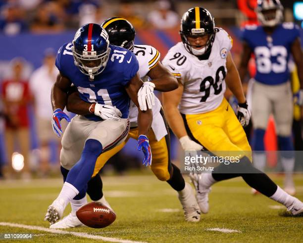 Khalid Abdullah of the New York Giants drops the ball as Keith Kelsey and TJ Watt of the Pittsburgh Steelers defend during an NFL preseason game at...