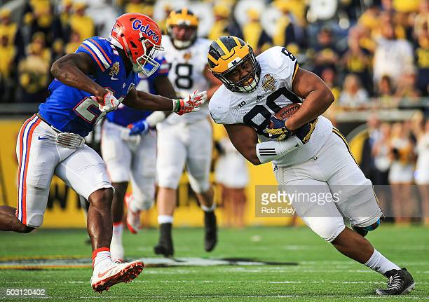 Khalid Hill of the Michigan Wolverines is pressured by Marcus Maye of the Florida Gators during the second half of the Buffalo Wild Wings Citrus Bowl...