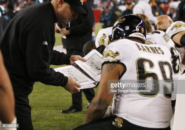 Khalif Barnes of the Jacksonville Jaguars on the sidelines studies the playbook with his coach during the AFC Divisional Playoff game played on...