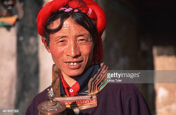 Khampa man in the former Tibetan kingdom of Kham Khampa men are identified by vibrant head bands of red silk string that is wrapped around their...