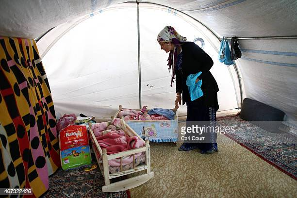 Khanon Hamo from Kobani tends to her 7monthold twins in her tent in a refugee camp on March 22 2015 in Suruc in the province of Sanliurfa Turkey...