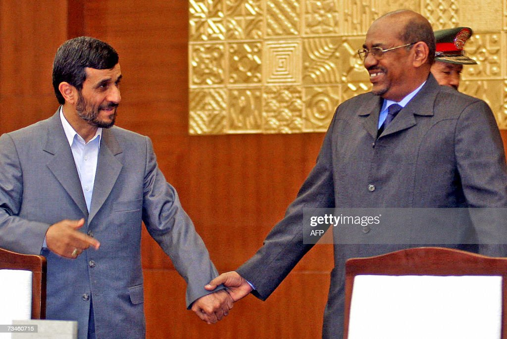 Iranian President Mahmoud Ahmadinejad holds Sudanese President Omar alBechir's hands after they signed an agreement in Khartoum 01 March 2007 Iran...
