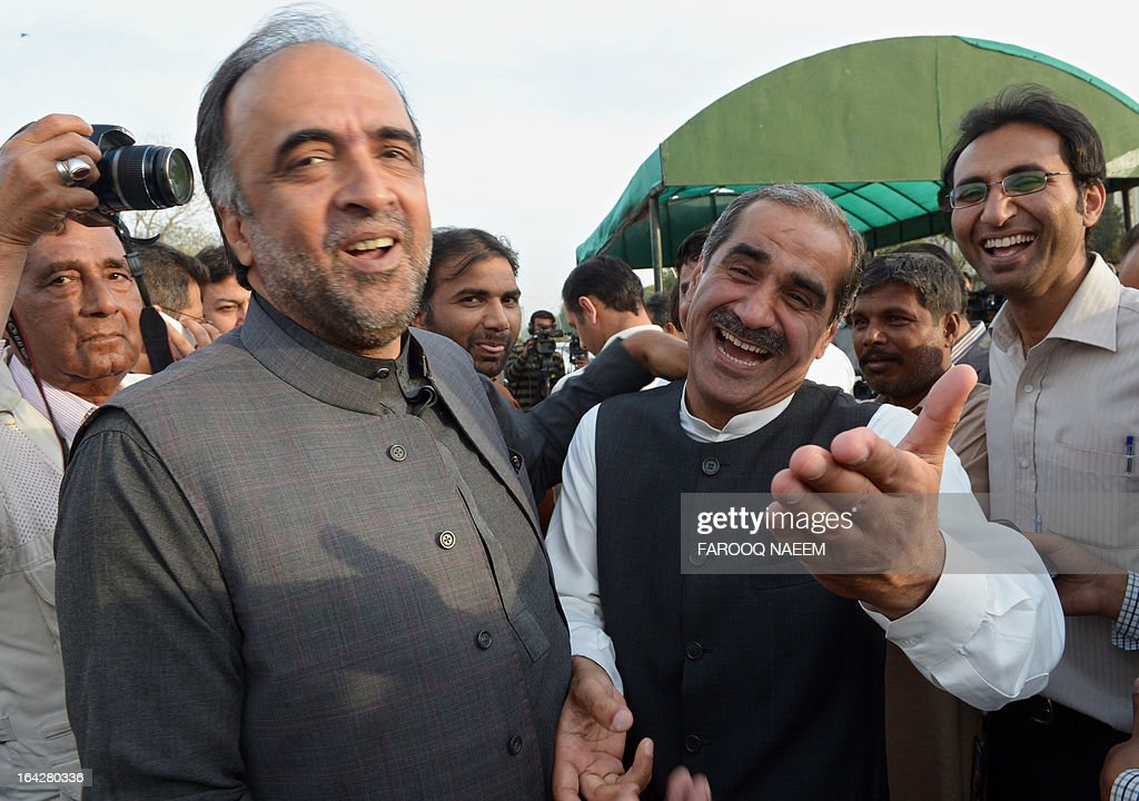 Khawaja Saad Rafique (R), opposition leader of Pakistan Muslim League Nawaz party shares a light movement with former information minister Qamar Zaman Kaira (L) after attending a meeting to discuss the caretaker prime minister outside the parliament house in Islamabad on March 22, 2013. Pakistan will go to the polls on May 11, the presidency announced March 20, in an historic general election marking the first democratic transition of power in the country's 66-year existence. AFP PHOTO/ Farooq NAEEM