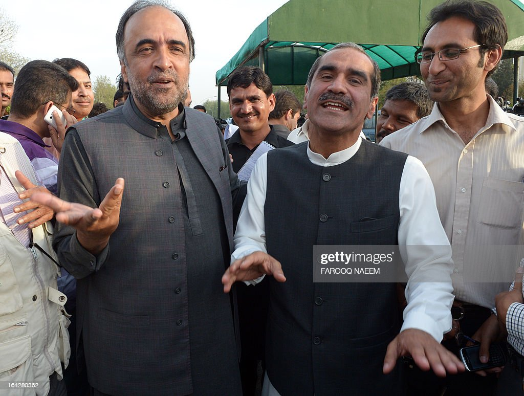 Khawaja Saad Rafique (2R), opposition leader of Pakistan Muslim League Nawaz party shares a light movement with former information minister Qamar Zaman Kaira (L) after attending a meeting to discuss the caretaker prime minister outside the parliament house in Islamabad on March 22, 2013. Pakistan will go to the polls on May 11, the presidency announced March 20, in an historic general election marking the first democratic transition of power in the country's 66-year existence. AFP PHOTO/ Farooq NAEEM