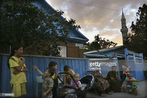 Khazak women and children gather outside their homes where a mosque minaret towers in the background at dusk August 9 2006 in Icic a town about an...