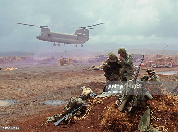 US Chinook helicopter lowers supplies by cable sling onto field as GI's avoid airstream created by rotor blades