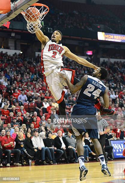 Khem Birch of the UNLV Rebels dunks over JoJo McGlaston of the Utah State Aggies during their game at the Thomas Mack Center on January 22 2014 in...