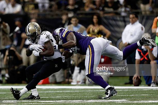 Khiry Robinson of the New Orleans Saints is brought down by Jasper Brinkley of the Minnesota Vikings during a game at the MercedesBenz Superdome on...