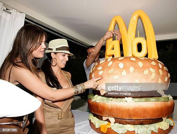 Khloe Kardashian and Kim Kardashian look at a giant 'Big Mac' burgerthemed birthday cake during the McDonald's Big Mac 40th Birthday Party at Project...