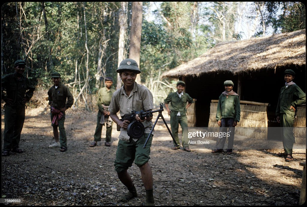 Khmer Rouge guerrillas fool around with captured Vietnamese uniforms and a machine gun after taking a Vietnamese bunker complex in the Cardamom Mountains of Cambodia, 22th February 1981.