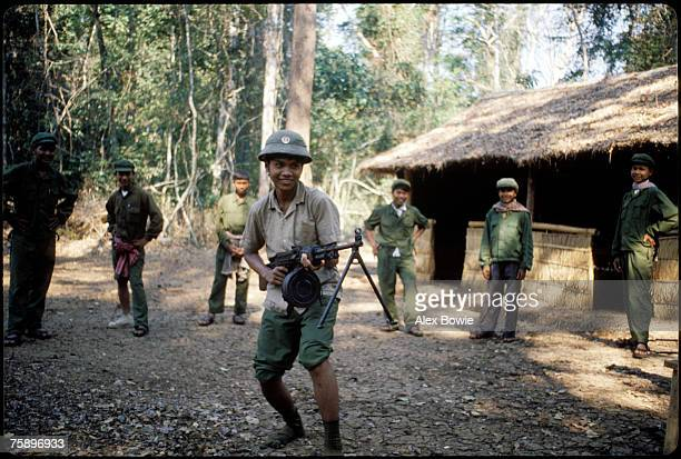 Khmer Rouge guerrillas fool around with captured Vietnamese uniforms and a machine gun after taking a Vietnamese bunker complex in the Cardamom...