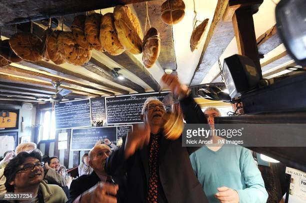 Khokon Ray from Horndon hangs a hot cross bun from the beam at The Bell Inn High Road Horndononthe Hill Essex