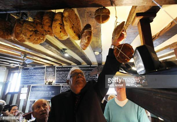 Khokon Ray of Horndon hangs a hot cross bun from the beam at The Bell Inn High Road Horndononthe Hill Essex