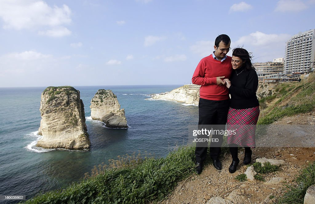 Kholoud Sukkariyeh (R) and Nidal Darwish, who got married in defiance of Lebanon's ban on civil unions, walk past Beiurt's landmark Pigeon Rock on January 25, 2013. The couple, from different Muslim sects, recited their vows in an intimate ceremony late last year at Sukkarieh's home with her brother as witness. The Lebanese authorities recognise civil weddings only if they have been registered abroad, and it has become common for mixed-faith couples to marry in nearby Cyprus. AFP PHOTO/JOSEPH EID