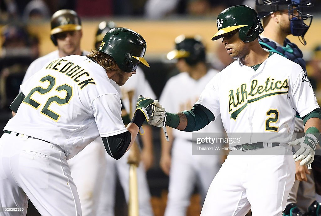 Khris Davis #2 and Josh Reddick #22 of the Oakland Athletics celebrates after Davis hit a two-run homer against the Seattle Mariners in the bottom of the seventh inning at O.co Coliseum on May 2, 2016 in Oakland, California.