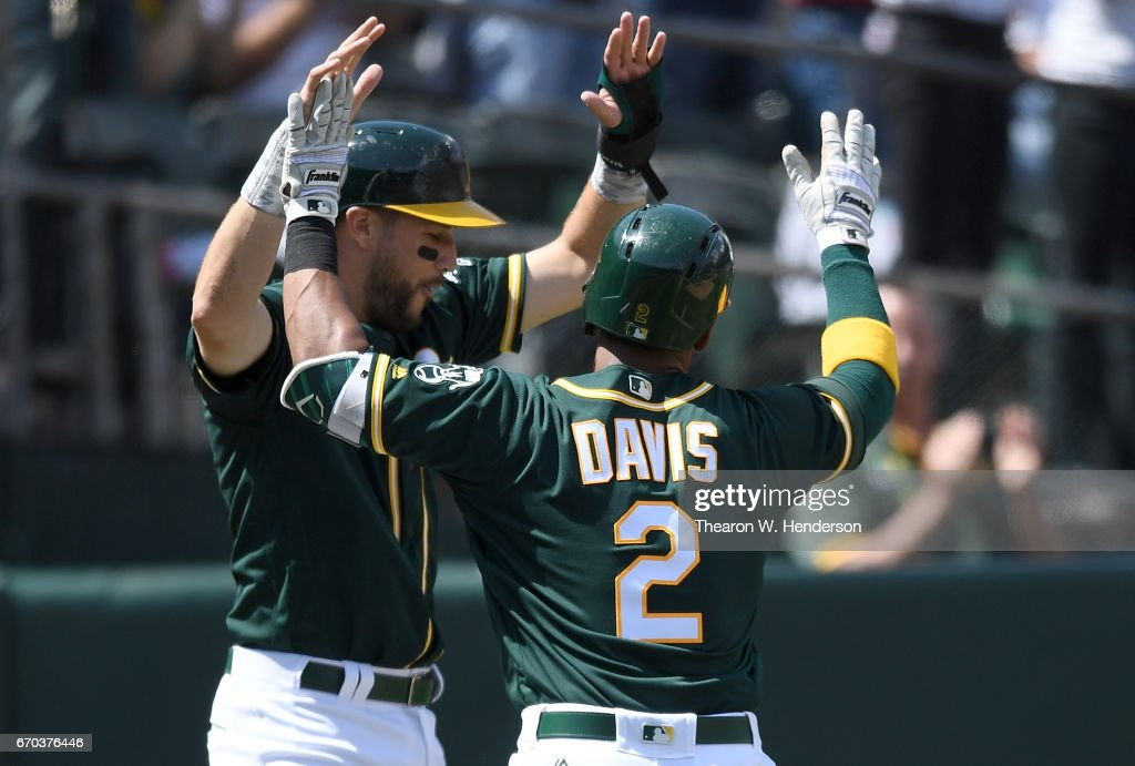 Khris Davis #2 and Trevor Plouffe #3 of the Oakland Athletics celebrate after Davis' two-run homer against the Texas Rangers in the bottom of the fifth inning at Oakland Alameda Coliseum on April 19, 2017 in Oakland, California.