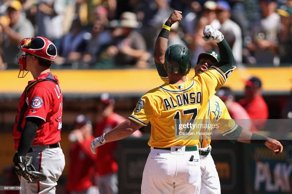 Khris Davis #2 and Yonder Alonso #17 of the Oakland Athletics celebrate after Alonso hit a two run home run against the Washington Nationals during the seventh inning of the MLB game at Oakland Coliseum on June 3, 2017 in Oakland, California. The Athletics defeated the Nationals 10-4.