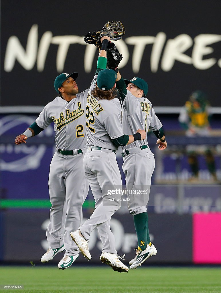 Khris Davis #2, Josh Reddick #22 and Billy Burns #1 of the Oakland Athletics celebrate after defeating the New York Yankees 5-2 at Yankee Stadium on April 20, 2016 in the Bronx borough of New York City.