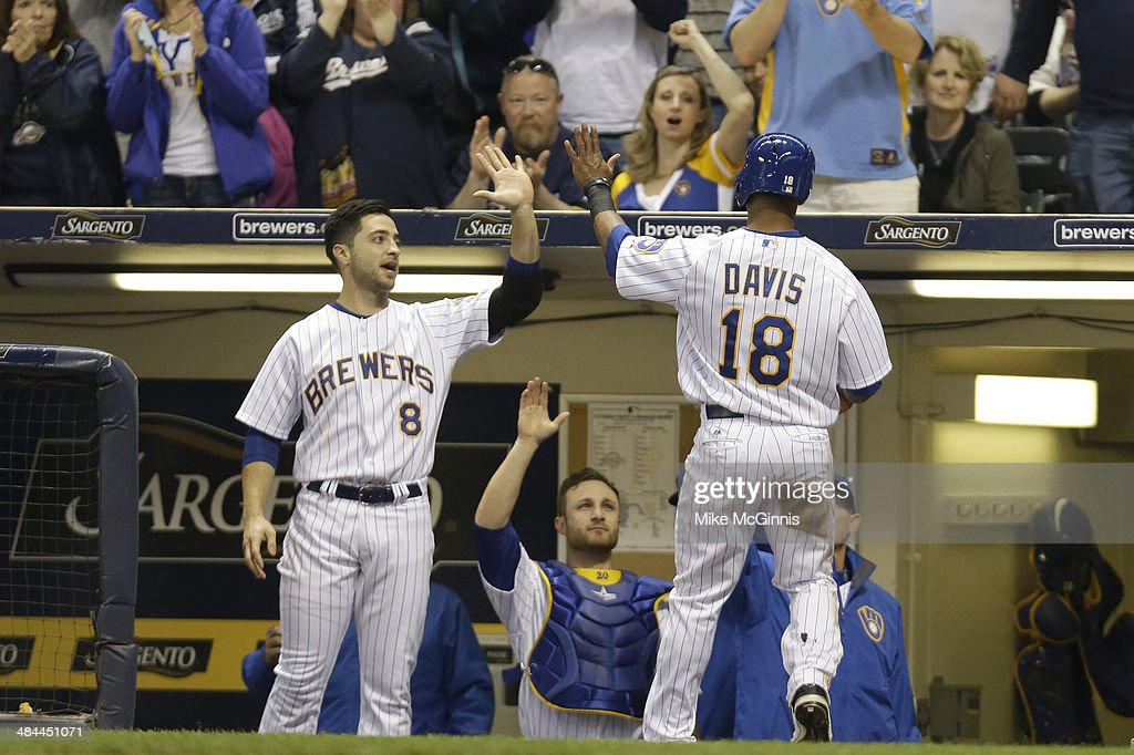 Khris Davis #18 of the Milwaukee Brewers celebrates with Ryan Braun #8 after reaching home plate on a wild pitch by Edinson Volquez #36 of the Pittsburgh Pirates during the bottom of the second inning at Miller Park on April 12, 2014 in Milwaukee, Wisconsin.