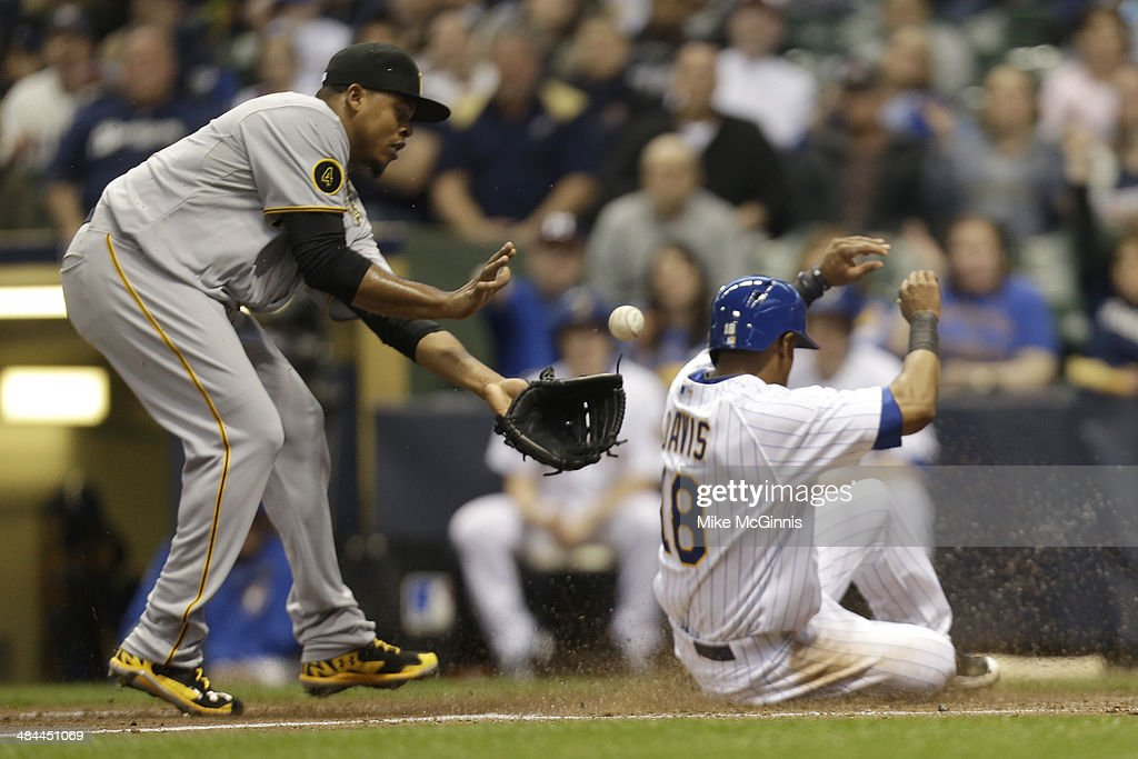 Khris Davis #18 of the Milwaukee Brewers makes it home plate on a wild pitch by Edinson Volquez #36 of the Pittsburgh Pirates during the bottom of the second inning at Miller Park on April 12, 2014 in Milwaukee, Wisconsin.