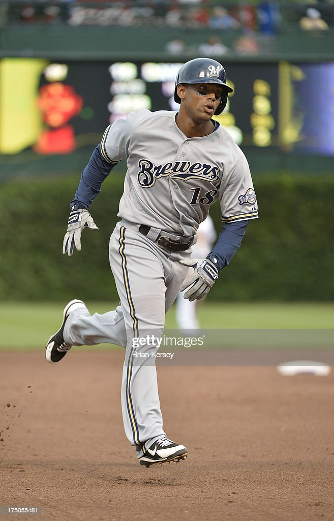 Khris Davis #18 of the Milwaukee Brewers rounds the bases after hitting a three-run home run scoring teammates Jeff Bianchi #14 and Yuniesky Betancourt #3 during the seventh inning at Wrigley Field on July 30, 2013 in Chicago, Illinois.