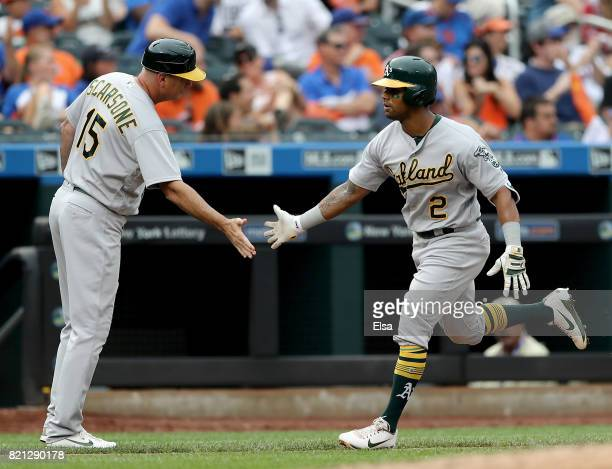 Khris Davis of the Oakland Athletics celebrates his solo home run with third base coach Steve Scarsone in the fourth inning against the New York Mets...