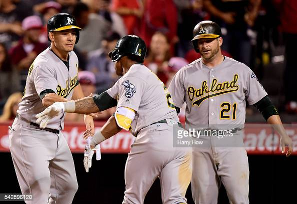 Khris Davis of the Oakland Athletics celebrates his three run homerun with Danny Valencia and Stephen Vogt to take a 74 lead over the Los Angeles...