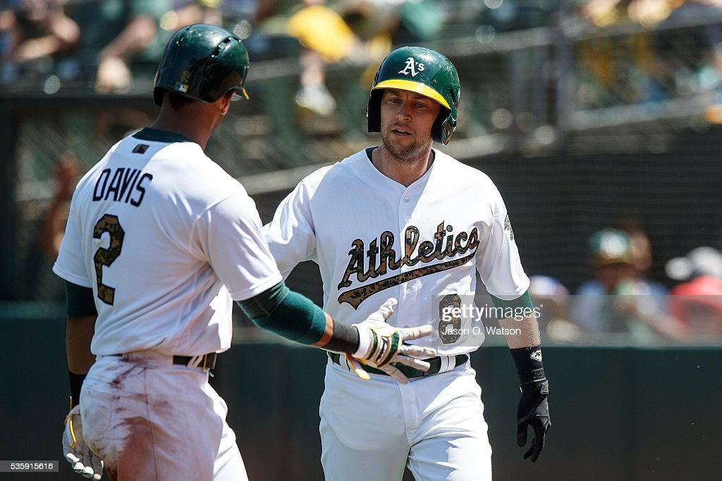 <a gi-track='captionPersonalityLinkClicked' href=/galleries/search?phrase=Khris+Davis+-+Baseball+Player&family=editorial&specificpeople=7890487 ng-click='$event.stopPropagation()'>Khris Davis</a> #2 of the Oakland Athletics is congratulated after hitting a sacrifice fly ball to drive in <a gi-track='captionPersonalityLinkClicked' href=/galleries/search?phrase=Jed+Lowrie&family=editorial&specificpeople=4949369 ng-click='$event.stopPropagation()'>Jed Lowrie</a> #8 during the sixth inning against the Minnesota Twins at the Oakland Coliseum on May 30, 2016 in Oakland, California. The Oakland Athletics defeated the Minnesota Twins 3-2.