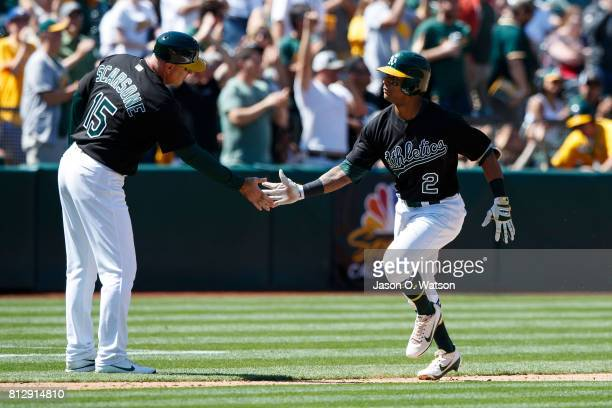 Khris Davis of the Oakland Athletics is congratulated by acting third base coach Steve Scarsone after hitting a two run home run against the Atlanta...