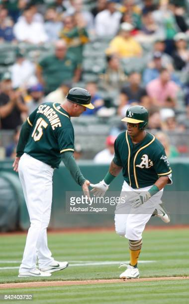 Khris Davis of the Oakland Athletics is congratulated by Acting Third Base Coach Steve Scarsone while running the bases after hitting a home run...
