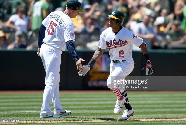 Khris Davis of the Oakland Athletics is congratulated by third base coach Steve Scarsone after Davis hit a solo home run against the Atlanta Braves...