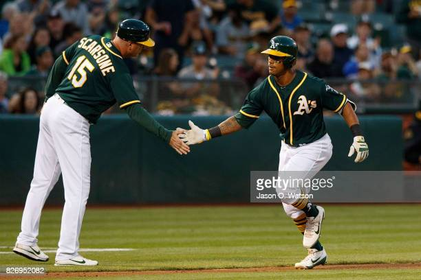 Khris Davis of the Oakland Athletics is congratulated by third base coach Steve Scarsone after hitting a home run against the Tampa Bay Rays during...