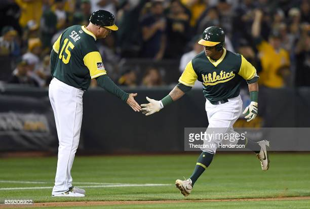 Khris Davis of the Oakland Athletics is congratulated by third base coach Steve Scarsone after Davis hit a solo home run against the Texas Rangers in...