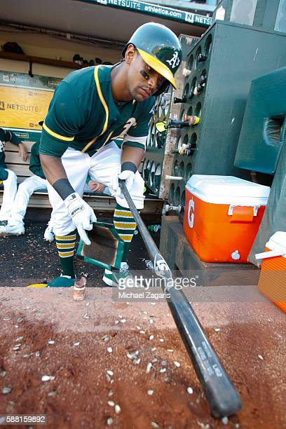 Khris Davis of the Oakland Athletics runs pine tar on his bat handle in he dugout during the game against the Tampa Bay Rays at the Oakland Coliseum...