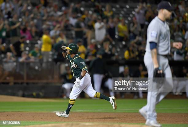 Khris Davis of the Oakland Athletics salutes as he trots around the bases after hitting a tworun homer off of James Paxton of the Seattle Mariners in...