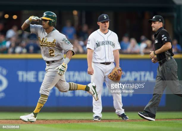 Khris Davis of the Oakland Athletics salutes his dugout after hitting a home run in the third inning as Kyle Seager of the Seattle Mariners reacts at...