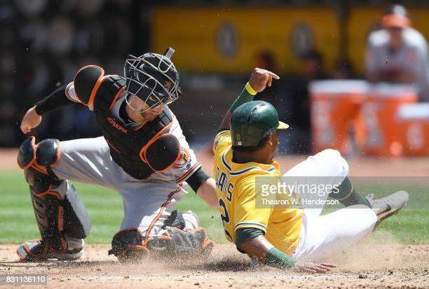 Khris Davis of the Oakland Athletics scores sliding past the tag of Caleb Joseph of the Baltimore Orioles in the bottom of the fourth inning at...