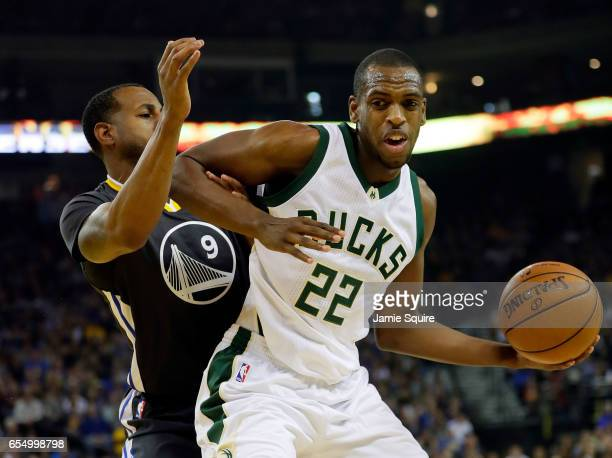 Khris Middleton of the Milwaukee Bucks controls the ball as Andre Iguodala of the Golden State Warriors defends during the game at ORACLE Arena on...