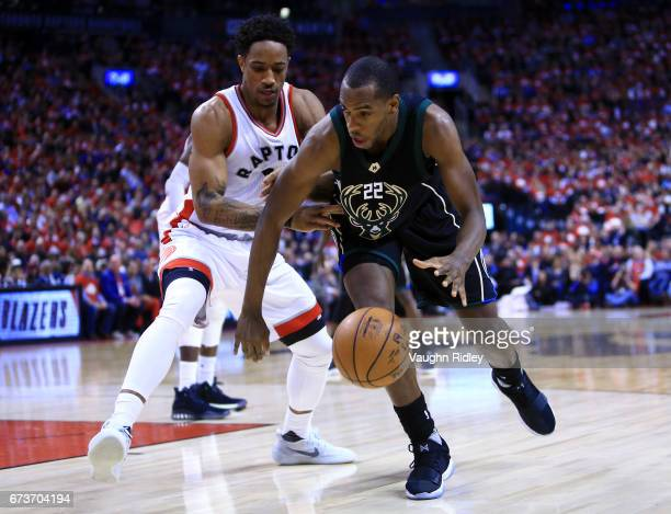 Khris Middleton of the Milwaukee Bucks dribbles the ball as DeMar DeRozan of the Toronto Raptors defends in the second half of Game Five of the...