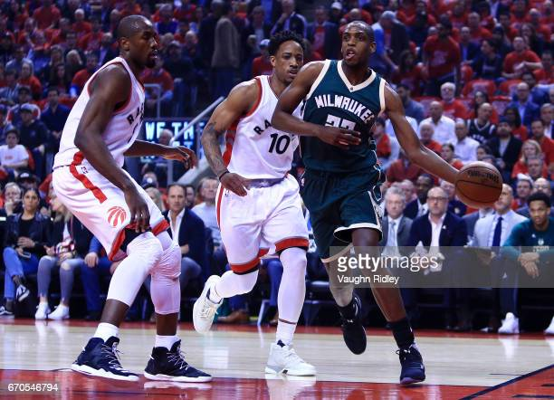 Khris Middleton of the Milwaukee Bucks dribbles the ball as Serge Ibaka and DeMar DeRozan of the Toronto Raptors defend in the first half of Game Two...