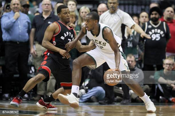Khris Middleton of the Milwaukee Bucks dribbles the ball while being guarded by Kyle Lowry of the Toronto Raptors in the fourth quarter in Game Six...