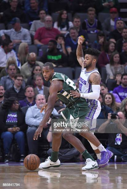 Khris Middleton of the Milwaukee Bucks dribbles the ball while defended by Frank Mason III of the Sacramento Kings during their NBA basketball game...