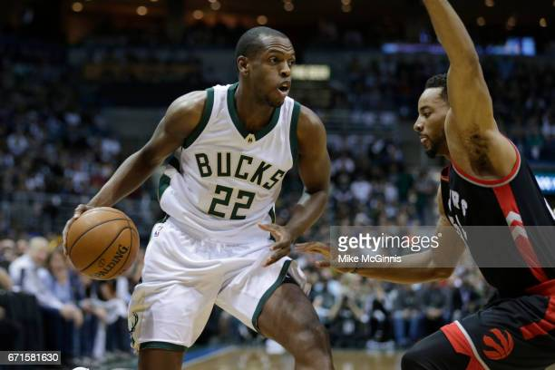 Khris Middleton of the Milwaukee Bucks drives to the hoop with Norman Powell the Toronto Raptors during the first half of Game Four of the Eastern...