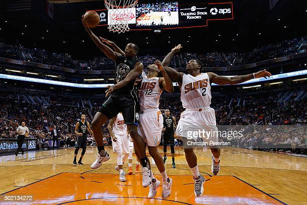 Khris Middleton of the Milwaukee Bucks lays up a shot past TJ Warren and Eric Bledsoe of the Phoenix Suns during the second half of the NBA game at...