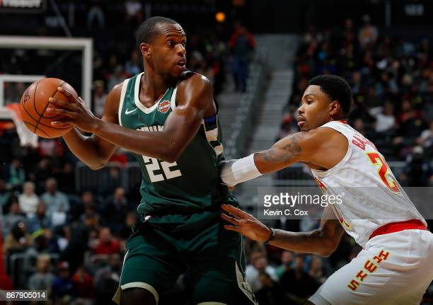 Khris Middleton of the Milwaukee Bucks looks to pass against Kent Bazemore of the Atlanta Hawks at Philips Arena on October 29 2017 in Atlanta...