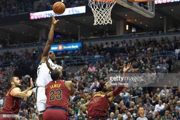 Khris Middleton of the Milwaukee Bucks shoots over LeBron James and JR Smith of the Cleveland Cavaliers during the first quarter of a game at the...