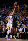 Khris Middleton of the Milwaukee Bucks shoots over Stephen Curry of the Golden State Warriors at ORACLE Arena on December 18 2015 in Oakland...