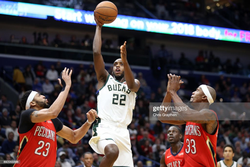 Khris Middleton #22 of the Milwaukee Bucks shoots the ball over Anthony Davis #23 of the New Orleans Pelicans at Smoothie King Center on December 13, 2017 in New Orleans, Louisiana.