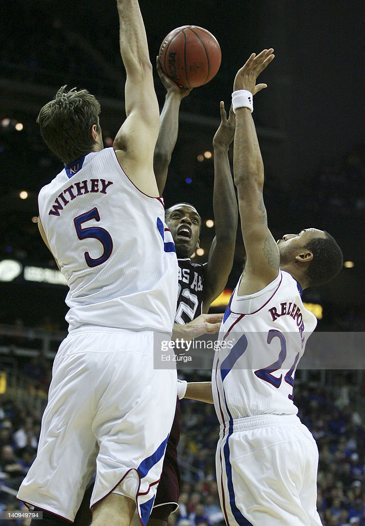 Khris Middleton #22 of the Texas A&M Aggies shoots between Jeff Withey #5 and Travis Releford #24 of the Kansas Jayhawks during the quarterfinals of the Big 12 Basketball Tournament March 8, 2012 at Sprint Center in Kansas City, Missouri.