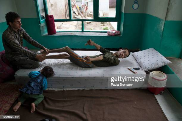 Khuja Fareed a quadriplegic gets readjusted on his bed by his brother Hamid at his home in Kabul on March 22 2016 He is now a quadrapalegic injured...
